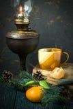 葡萄酒圣诞节大气:煤油灯,书,蜜桔 免版税库存图片