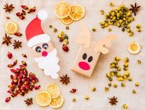 葡萄酒圣诞节工艺在亚麻制桌布的礼物盒与切片柠檬、香料和装饰 免版税库存照片