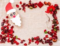 葡萄酒圣诞节工艺在亚麻制桌布的礼物盒与红色芳香花和草本 免版税库存照片