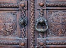 葡萄酒在一个木古色古香的门的狮子门把 库存图片