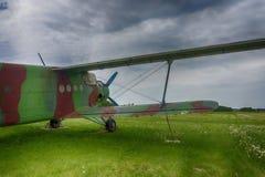 葡萄酒在一个豪华的绿色领域停放的绿色双翼飞机 免版税库存照片