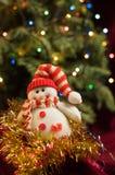 葡萄酒在圣诞树的背景的新年雪人 免版税库存照片