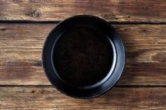 葡萄酒在木土气背景的生铁平底锅 免版税库存图片