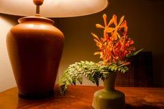 葡萄酒在木桌上的台灯光与花 免版税库存照片