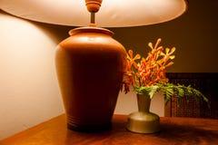 葡萄酒在木桌上的台灯光与花 免版税图库摄影
