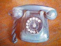 葡萄酒在木棕色桌上的拨号电话 库存照片