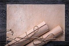 葡萄酒在木背景的滚动的被捆绑的纸 免版税库存照片