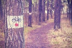 葡萄酒在森林里定了调子自行车在一棵树绘的足迹标志 免版税库存照片
