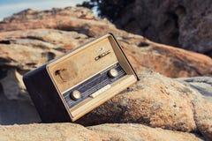 葡萄酒在海滩的被塑造的老收音机 免版税库存照片
