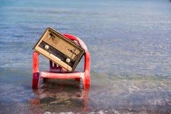 葡萄酒在海滩的被塑造的老收音机 图库摄影