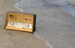 葡萄酒在海滩的被塑造的老收音机 库存照片