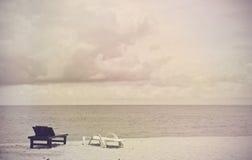 葡萄酒在海滩的轻便折叠躺椅 免版税库存照片