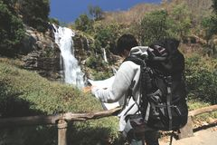 葡萄酒在瀑布国家公园定了调子看在他的手上的年轻亚裔背包徒步旅行者的图象地图 库存图片