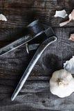 葡萄酒在老木backgorund的大蒜压榨机 免版税库存图片