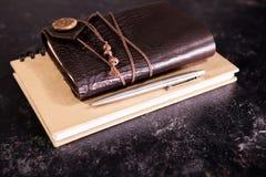 葡萄酒在铅笔旁边变老了在日志的笔记本 库存图片