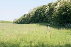 葡萄酒在绿色草甸的照相机三脚架 免版税库存图片