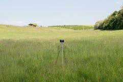 葡萄酒在绿色草甸的照相机三脚架 库存照片