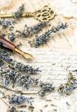 葡萄酒墨水笔、钥匙、淡紫色花和老情书 库存照片
