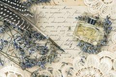 葡萄酒墨水笔、香水、淡紫色花和老情书 免版税库存照片
