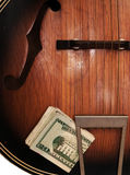 葡萄酒声学吉他和金钱 免版税库存图片