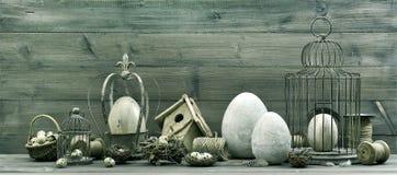 葡萄酒复活节装饰用鸡蛋、巢和鸟笼 免版税图库摄影