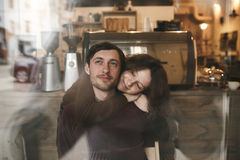 葡萄酒夫妇拥抱和笑 在豆咖啡杯新鲜的界面附近 免版税库存图片