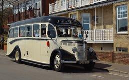 葡萄酒奶油和黑色贝得福得公车运送被驾驶沿街道 免版税图库摄影