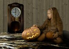 葡萄酒孩子 万圣夜、逗人喜爱的小女孩坐在南瓜旁边的发光和神色在时钟 库存照片