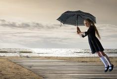 葡萄酒孩子 升空 有一把伞的女孩在海日落背景  免版税图库摄影