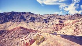 葡萄酒定了调子一条沙漠路的pictue在火,美国谷的  免版税库存照片