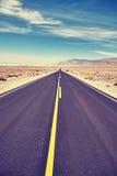 葡萄酒定了调子一条风景沙漠路的图片 免版税库存照片