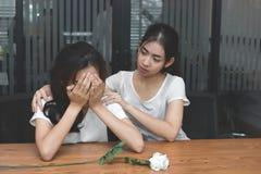 葡萄酒定了调子安慰一个哀伤的沮丧的女性朋友的沮丧的被注重的亚裔妇女的图象 破坏或最佳的关系骗局 库存照片