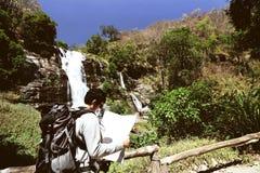 葡萄酒定了调子年轻在他的手上的背包徒步旅行者探索的地图的图象在瀑布国家公园背景中 免版税库存照片