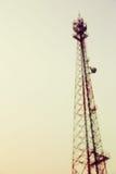 葡萄酒定了调子并且弄脏了电力量在苍白天空背景的岗位塔 免版税库存图片