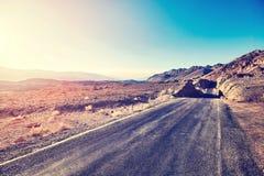 葡萄酒定了调子沙漠路的图片在日落 免版税库存照片