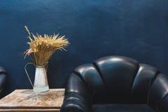 葡萄酒家具和装饰、深蓝墙壁有一部分的葡萄酒皮革扶手椅子和花瓶有花的在旁边桌上 图库摄影
