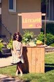葡萄酒小女孩和她的柠檬水摊 免版税库存图片