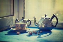 葡萄酒小杯子,在一张蓝色桌上的钢茶壶 免版税库存照片