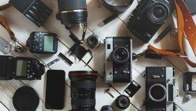 葡萄酒影片照相机、数字照相机和智能手机在白色木背景技术开发概念 顶视图 免版税库存图片