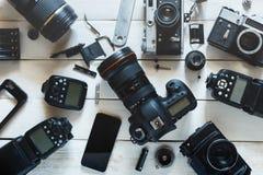 葡萄酒影片照相机、数字照相机和智能手机在白色木背景技术开发概念 顶视图 库存照片