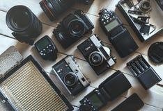 葡萄酒影片照相机、DSLR数字照相机和辅助部件在白色木背景技术开发概念 顶视图 免版税库存图片