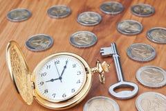 葡萄酒怀表和一把钥匙反对欧洲硬币。 免版税图库摄影