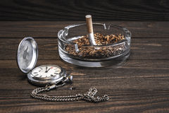 葡萄酒怀表和被弄皱的香烟在玻璃烟灰缸 库存图片