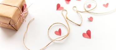 葡萄酒情人节在白色背景的礼物盒 桃红色纸弓,黄麻绳索,情书长的横幅 库存图片