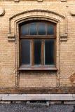 葡萄酒成拱形在黄色砖墙壁的窗口  在一个褐红的深红木制框架的黑玻璃 古董的概念 免版税库存图片