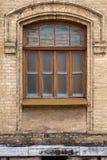 葡萄酒成拱形在黄色砖墙壁的窗口  在一个褐红的深红木制框架的黑玻璃 古董的概念 库存图片