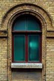 葡萄酒成拱形在黄色砖墙壁的窗口  绿色-海在一褐红深红木的波浪玻璃的颜色 免版税库存图片