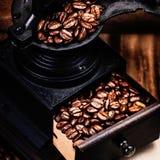 葡萄酒手工磨咖啡器用在木褐色的咖啡豆 免版税库存图片