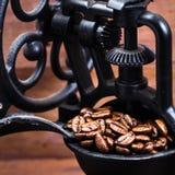 葡萄酒手工磨咖啡器用在木褐色的咖啡豆 免版税图库摄影