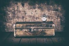 葡萄酒手提箱和一个时钟在一个木地板上 免版税库存照片